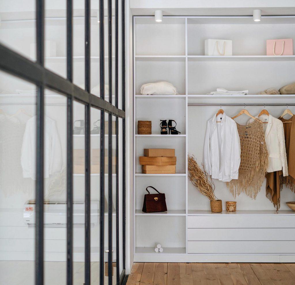 Dressing ouvert blanc qui met en valeur les accessoires de mode.