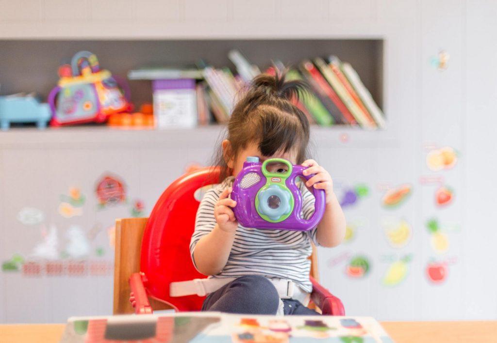 Enfant jouant dans une salle de jeux avec un appareil photo