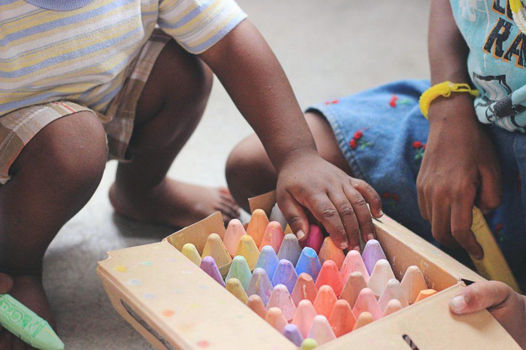 Enfant et parent jouant ensemble avec des craies dans une salle de jeux pour enfants